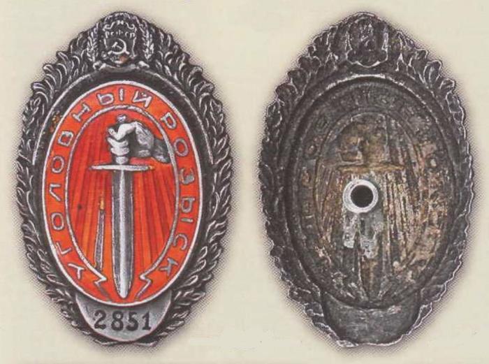 Знак сотрудника Центрального управления уголовного розыска (Центррозыск), который с 1927 года стал служебным знаком сотрудника активного состава угрозыска. В крепление на тыльной стороне знака (справа) с наружной стороны лацкана ввинчивался винт любого другого значка, например, комсомольского