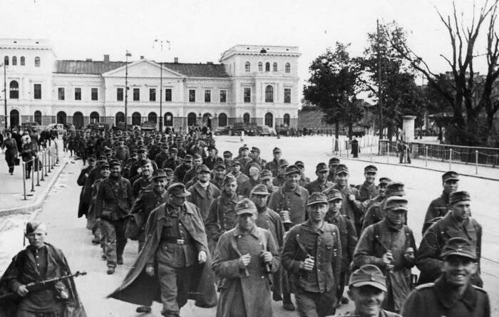 Колонна немецких военнопленных проходит мимо железнодорожного вокзала Риги