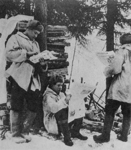 Финские солдаты читают газету с сообщением о заключении Московского договора, завершившего Зимнюю войну, март 1940 года