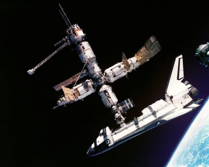 Орбитальная станция «Мир» с пристыкованным кораблем многоразового использования «Атлантис». Над «челноком» расположен стыковочный модуль, выше него — модуль «Кристалл», слева от него — модуль «Квант-2», справа — модуль «Спектр». Позади базового модуля — блок «Квант-1» (с длинной решетчатой фермой). Фотография сделана в 1995 году во время первой стыковки американского «челнока» с российской станцией